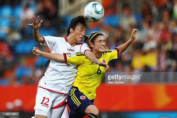 Jon Myong Hwa of Korea DPR is challenged by Daniela Montoya of Colombia during the FIFA Women's World Cup 2011 Group C match between Korea DPR and...