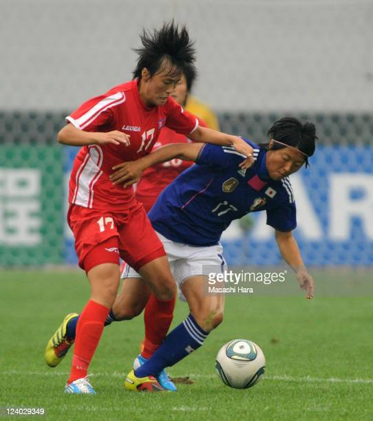 Jon Myong Hwa of North Korea and Yuki Nagasato of Japan compete for the ball during the London Olympic Women's Football Asian Qualifier match between...