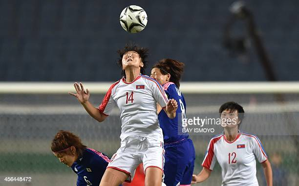 Jon MyongHwa of North Korea vies with Aya Miyama of Japan during their women's football final at Munhak Stadium during the Asian Games in Incheon on...