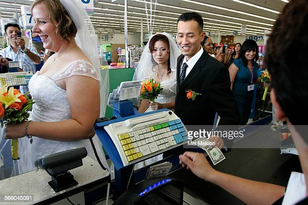 Jon Nguyen with his new bride Bonnie gives the cashier a dollar bill while paying the 99 cent fee for their wedding held inside the 99 cents only...