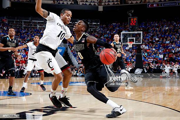 Jon Octeus of the Purdue Boilermakers drives to the basket against Troy Caupain of the Cincinnati Bearcats during the second round of the 2015 NCAA...