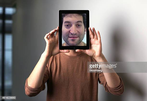 Jon Oringer billionaire and chief executive officer of Shutterstock Inc poses for a photograph holding an Apple Inc iPad following a Bloomberg...