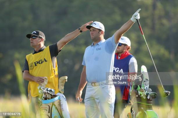 Jon Rahm of Spain and caddie Adam Hayes react to a tee shot by Tommy Fleetwood of England on the tenth tee during the second round of the 2021 PGA...