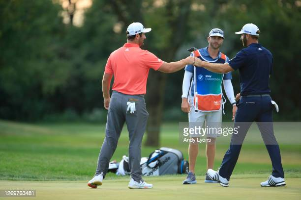 Jon Rahm of Spain and Dustin Johnson of the United States fist bump after Jon Rahm of Spain made a 66-foot putt on their first sudden-death playoff...