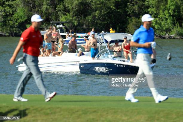 Jon Rahm of Spain and Dustin Johnson walk on the 14th hole while fans watch from a boat during the final match of the World Golf ChampionshipsDell...