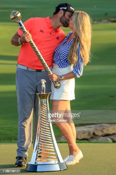 Jon Rahm of Spain and his fiancee Kelley Cahill pose with the DP World Tour Championship Trophy and the European Tour Race To Dubai Trophy after the...