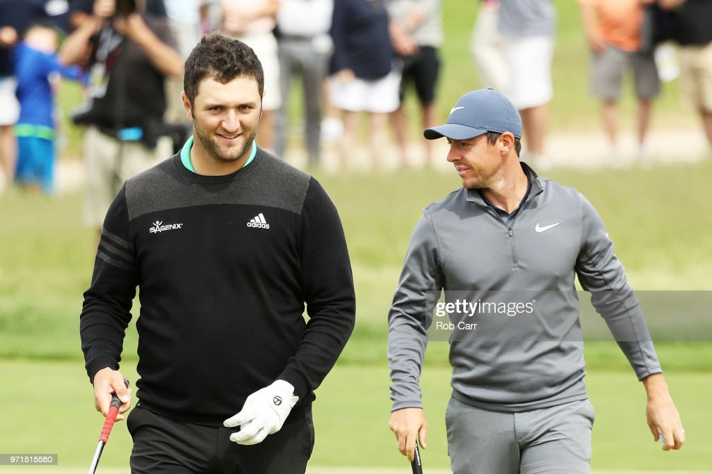 Jon Rahm (L) of Spain and Rory McIlroy of Northern Ireland stand on the 16th green during practice rounds prior to the 2018 U.S. Open at Shinnecock Hills Golf Club on June 11, 2018 in Southampton, New York.