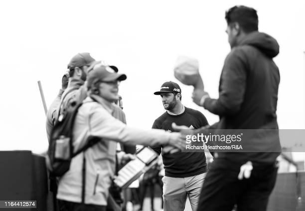 Jon Rahm of Spain and Tony Finau of the USA meet their walking scorers as they walk to the first tee during the final round of the 148th Open...