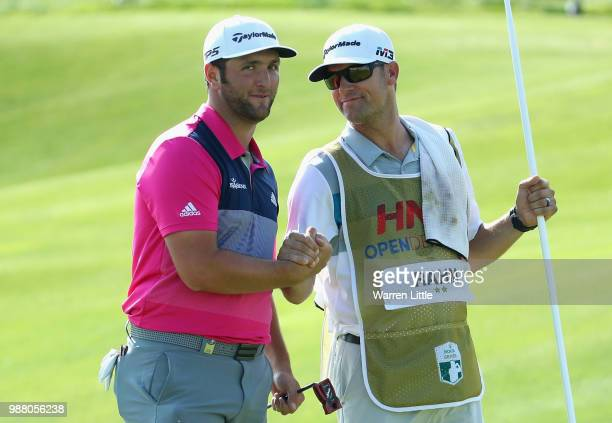 Jon Rahm of Spain celebrates a birdie with his caddie Adam Hayes on the 18th green during the third round of the HNA Open de France at Le Golf...