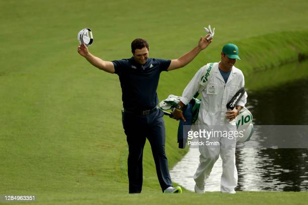 Jon Rahm of Spain celebrates with his Adam Hayes after skipping in for a hole in one on the 16th during a practice round prior to the Masters at...