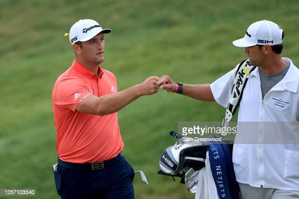 Jon Rahm of Spain celebrates with his caddie Adam Hayes after chipping in for birdie on the 16th hole during the final round of The Memorial...