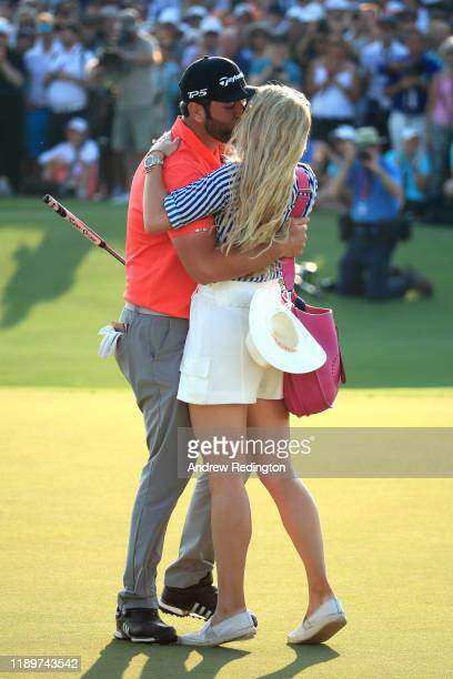 Jon Rahm of Spain celebrates with his fiance Kelley Cahill after putting in for a birdie on the eighteenth green to win the DP World Tour and Race to...