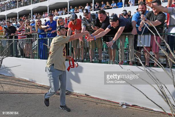 Jon Rahm of Spain gives gifts to fans at the 16th hole during the second round of the Waste Management Phoenix Open at TPC Scottsdale on February 2...