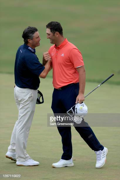 Jon Rahm of Spain is congratulated by Ryan Palmer of the United States after winning on the 18th green during the final round of The Memorial...