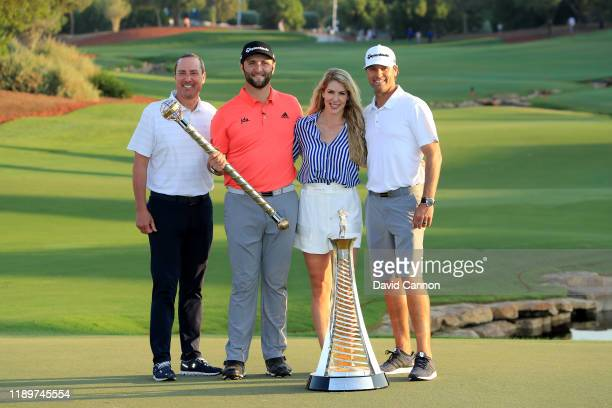 Jon Rahm of Spain Jeff Koski his business manager Adam Hayes his caddie and his fiancee Kelley Cahill pose with the DP World Tour Championship Trophy...