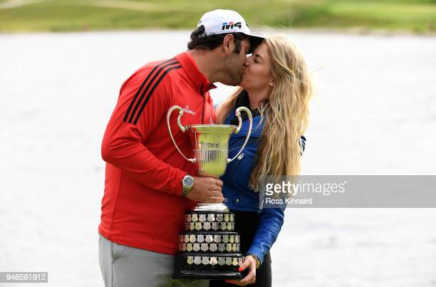 Jon Rahm of Spain kisses his girlfriend Kelley Cahill while holding the trophy after winning the Open de Espana during Day Four of the Open de Espana...