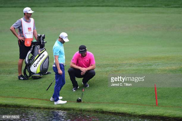 Jon Rahm of Spain measures his drop after hitting into a water hazard on the 12th hole while Wesley Bryan looks on during round two of the Wells...