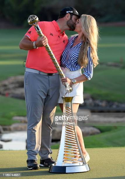 Jon Rahm of Spain poses with his fiance Kelley Cahill and the DP World Tour Championship trophy and the Race to Dubai trophy after the final round of...