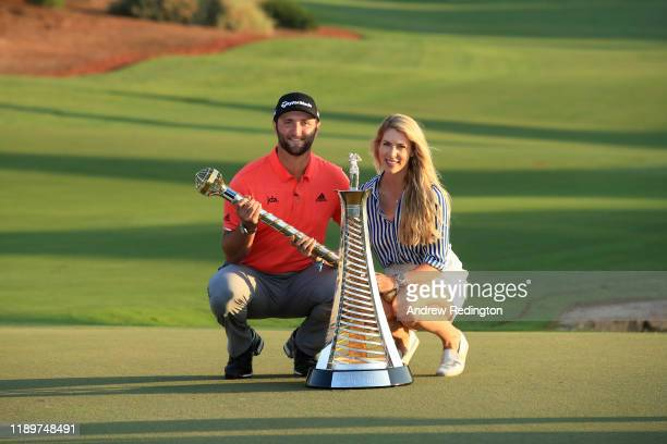 Jon Rahm of Spain poses with his fiance Kelley Cahill and the DP World Tour Championship trophy and the Race to Dubai trophy following his victory...