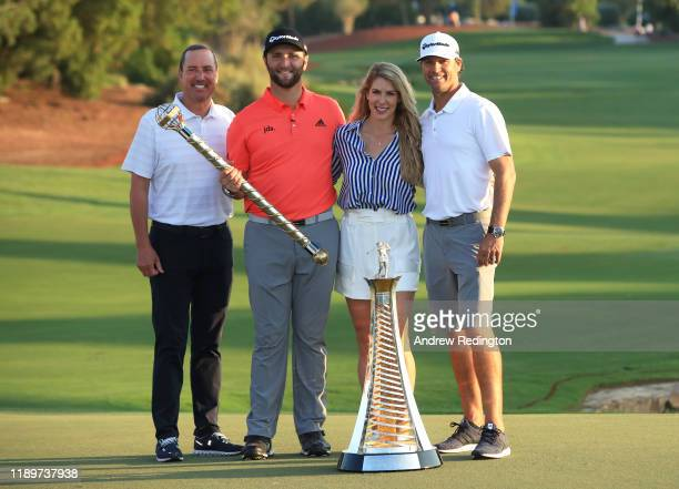 Jon Rahm of Spain poses with his manager fiance Kelley Cahill caddie Adam Hayes and the DP World Tour Championship trophy and the Race to Dubai...