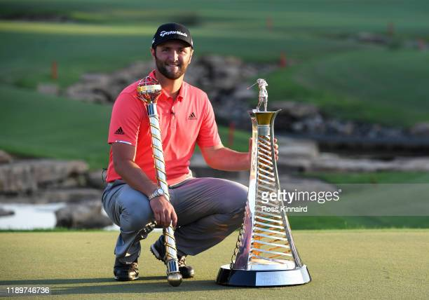 Jon Rahm of Spain poses with the DP World Tour Championship trophy and the Race to Dubai trophy following his victory during Day Four of the DP World...