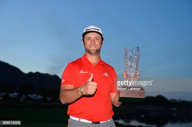 Jon Rahm of Spain poses with the trophy after putting in to win on the fourth hole of a sudden death playoff during the final round of the...