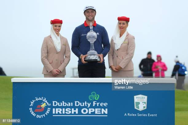 Jon Rahm of Spain poses with the trophy and Emirates girls after his victory during the final round of the Dubai Duty Free Irish Open at Portstewart...
