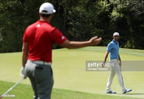 Jon Rahm of Spain reacts after playing a shot on the 2nd hole while Dustin Johnson looks on during the final match of the World Golf...