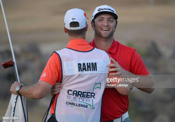 Jon Rahm of Spain reacts to his putt to win with caddie Adam Hayes on the fourth hole of a sudden death playoff during the final round of the...
