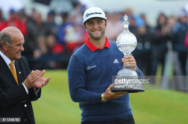 Jon Rahm of Spain receives the trophy from Colm McLoughlin the Executive Vice Chairman and CEO of Dubai Duty Free after his victory during the final...