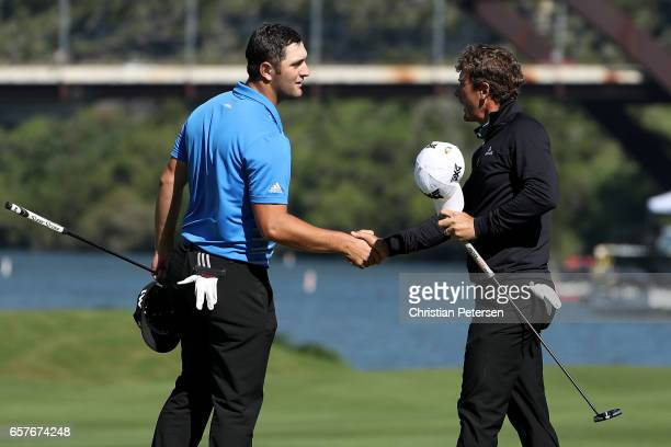 Jon Rahm of Spain shakes hands with Charles Howell III after winning their match 64 on the 14th hole during round four of the World Golf...