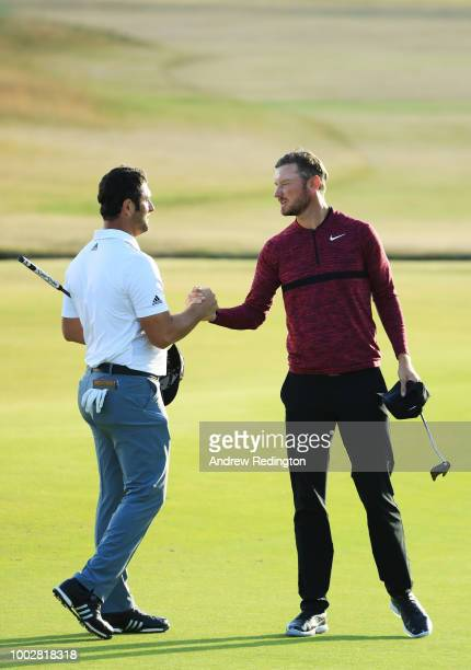 Jon Rahm of Spain shakes hands with Chris Wood of England on the 18th green during the second round of the 147th Open Championship at Carnoustie Golf...