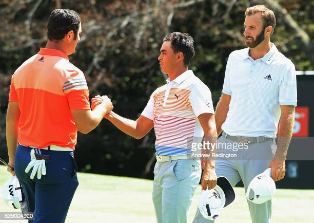 Jon Rahm of Spain shakes hands with Rickie Fowler of the United States on the ninth green as Dustin Johnson of the United States looks on during...