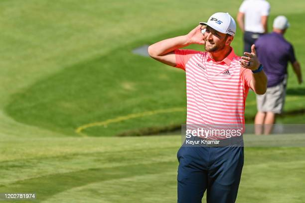 Jon Rahm of Spain smiles as he gestures to fans to get loud to celebrate his hole-in-one on the 17th hole during the third round of the World Golf...