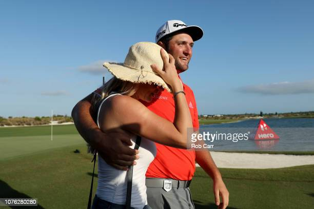 Jon Rahm of Spain walks off the 18th green with fiancee Kelley Cahill after winning the Hero World Challenge at Albany Bahamas on December 02 2018 in...