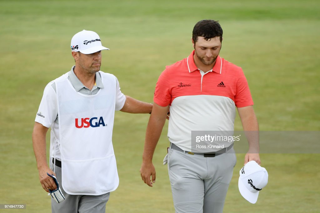 Jon Rahm of Spain walks off the 18th green with his caddie Adam Hayes during the first round of the 2018 U.S. Open at Shinnecock Hills Golf Club on June 14, 2018 in Southampton, New York.