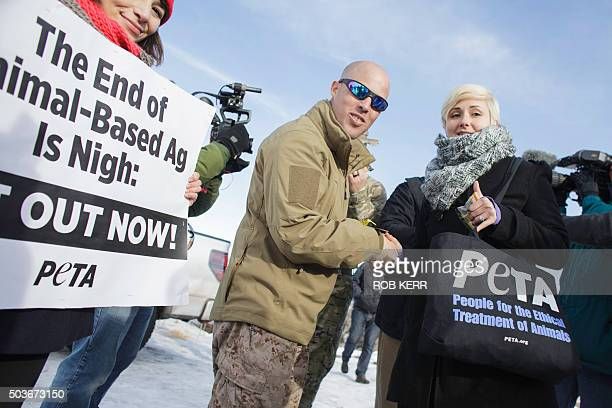 Jon Ritzheimer left and Lindsay Rajt pose for the media after eating meatless jerky products offered by PETA representatives at the entrance of the...