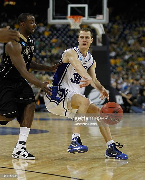 Jon Scheyer of the Duke Blue Devils passes the ball under pressure from Keaton Grant of the Purdue Boilermakers during the south regional semifinal...