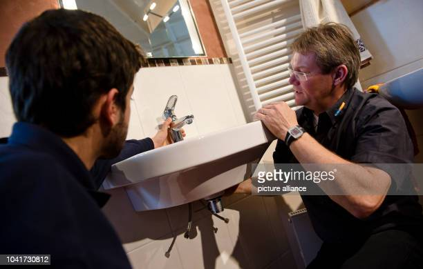 Jon Serrano from Spain and plumber Andreas Feucht take apart a sink in Bad Homburg Germany 16 April 2013 Four young Spanish trainees are working for...
