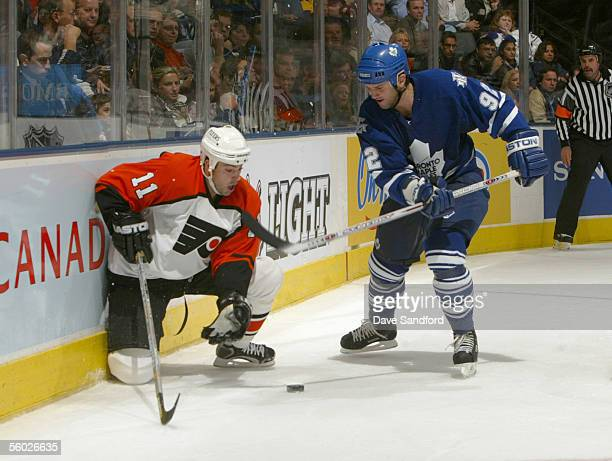 Jon Sim of the Philadelphia Flyers moves for the puck against Jeff O'Neill of the Toronto Maple Leafs during the NHL game at the Air Canada Centre on...