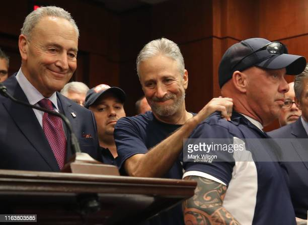 Jon Stewart hugs 911 first responder John Feal as Sen Charles Schumer stands nearby after the US Senate voted to renew permanent authorization of...