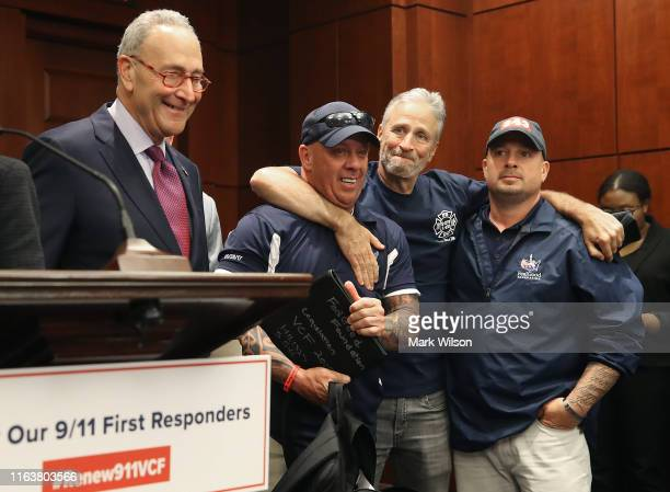 Jon Stewart hugs 911 first responders John Feal as Sen Charles Schumer stands nearby after the US Senate voted to renew permanent authorization of...