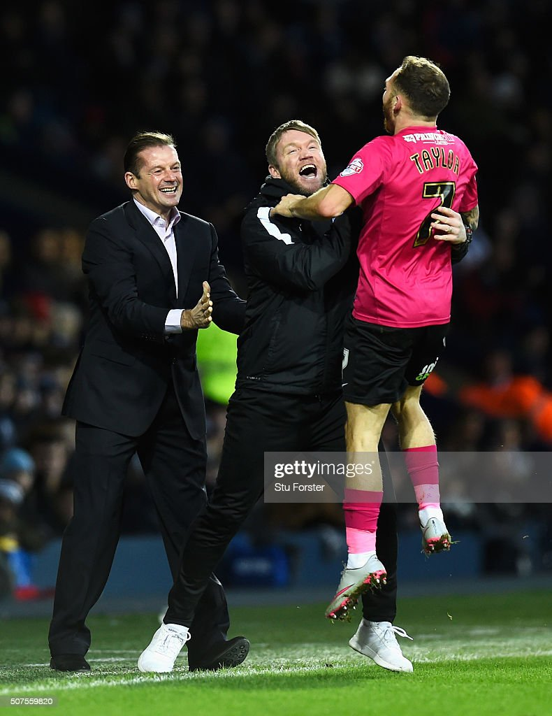 Jon Taylor (R) of Peterborough United celebrates scoring his team's second goal with manager Graham Westley (L) and staff during the Emirates FA Cup Fourth Round match between West Bromwich Albion and Peterborough United at The Hawthorns on January 30, 2016 in West Bromwich, England.
