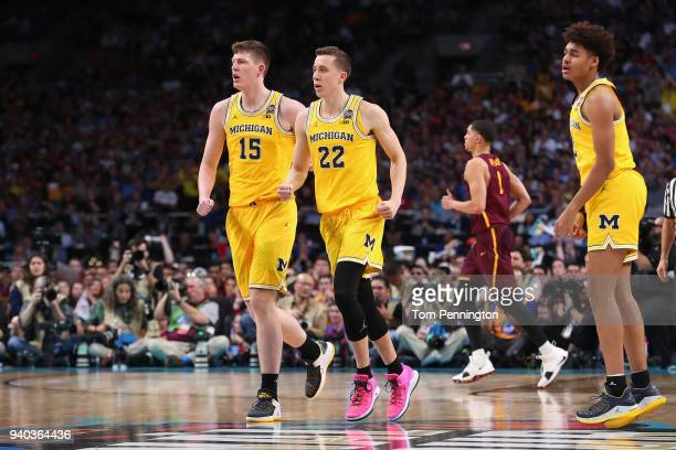 Jon Teske and Duncan Robinson of the Michigan Wolverines react in the second half against the Loyola Ramblers during the 2018 NCAA Men's Final Four...