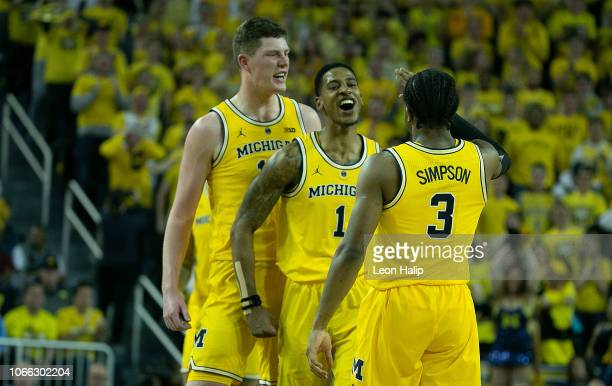 Jon Teske and teammates Charles Matthews and Zavier Simpson of the Michigan Wolverines celebrate a win over the North Carolina Tar Heels at Crisler...