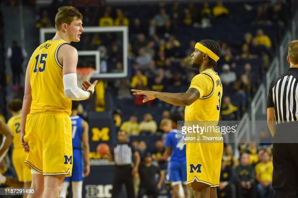 Jon Teske and Zavier Simpson of the Michigan Wolverines during a college basketball game against the Creighton Bluejays at Crisler Arena on November...