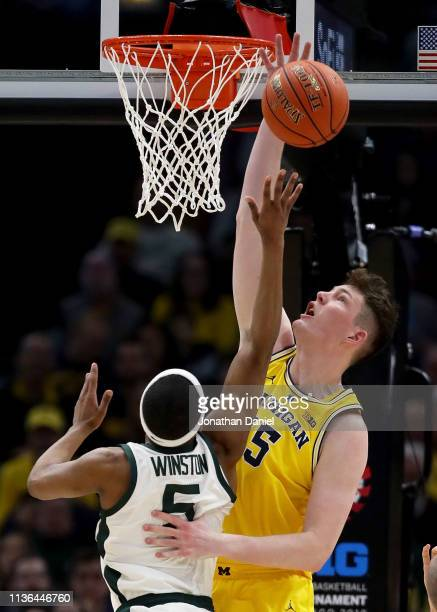 Jon Teske of the Michigan Wolverines blocks a shot attempt by Cassius Winston of the Michigan State Spartans in the first half during the...