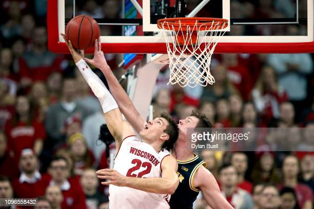 Jon Teske of the Michigan Wolverines blocks a shot attempt by Ethan Happ of the Wisconsin Badgers in the first half at the Kohl Center on January 19,...