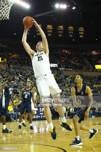 Jon Teske of the Michigan Wolverines gets to the basket next to Myreon Jones of the Penn State Nittany Lions during the first half at Crisler Arena...