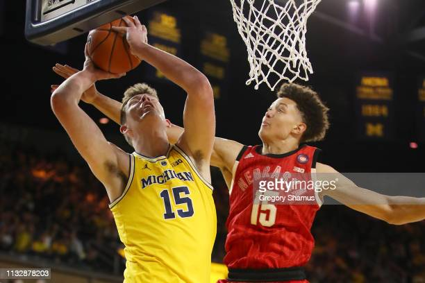 Jon Teske of the Michigan Wolverines tries to get a shot off past Isaiah Roby of the Nebraska Cornhuskers during the first half at Crisler Arena on...